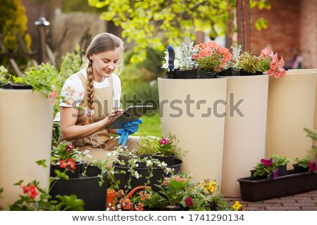 Young flower shop worker checking flowers Stock photo © pressmaster