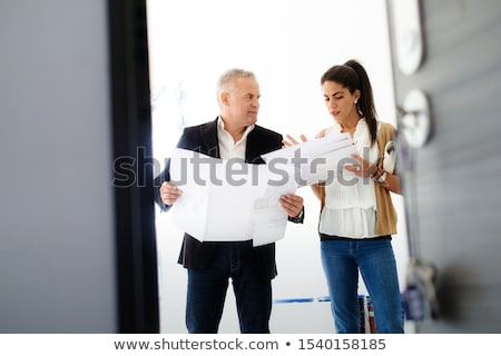 teamwork with boss and assistant looking at plans in building stock photo © diego_cervo