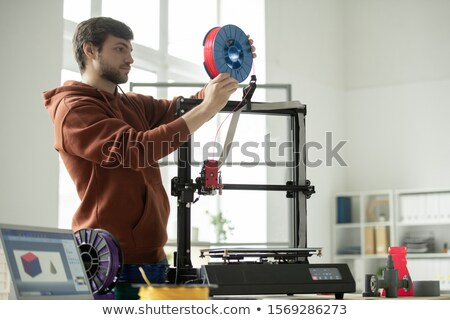 Young man putting new spool with red filament in 3d printer while going to print Stock photo © pressmaster