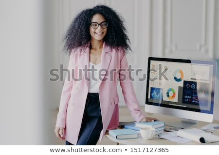 Half length shot of happy Afro woman dressed in elegant black clothes, keeps both hands on hips, wea Stock photo © vkstudio