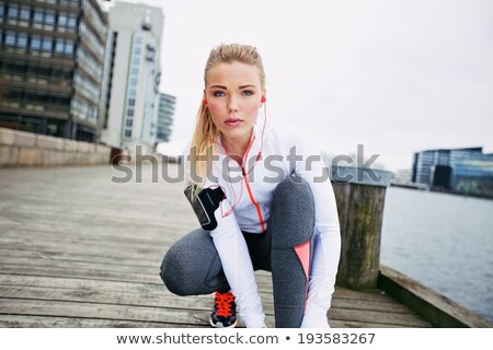 Woman athlete runner tie shoelaces and looking in camera. Stock photo © dmitroza