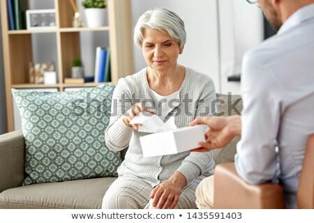 senior psychologist giving tissues to man patient Stock photo © dolgachov