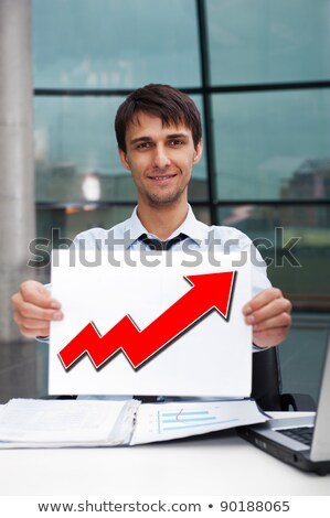 Attractive man in business suit with sign of up graph sitting at Stock photo © HASLOO
