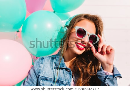 Woman in sunglasses listening to music through headphones Stock photo © photography33