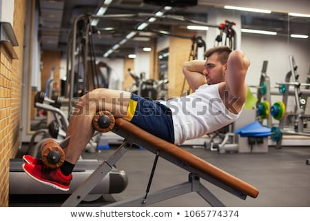 Athlete in a sit-ups bench Stock photo © texelart