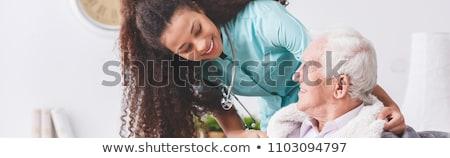Nurse helping to senior patient at home Stock photo © leventegyori