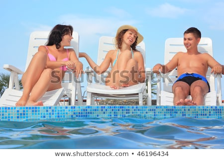 Smiling man and two young women reclining on chaise lounges open Stock photo © Paha_L