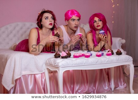 two attractive young women with cupcakes sitting in bed stock photo © deandrobot