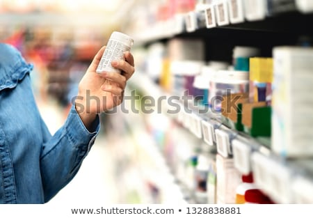 pharmacist looking at pills in bottle stock photo © is2