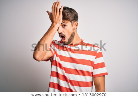 Image of frustrated adult man in striped t-shirt smiling and hol Stock photo © deandrobot