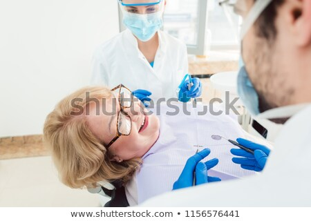 Team of dentists talking to senior patient in their surgery Stock photo © Kzenon
