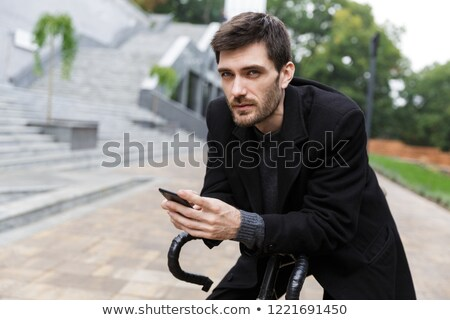 attractive young man dressed in coat leaning on a bicycle stock photo © deandrobot