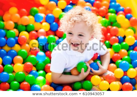 happy little kid boy playing at colorful plastic balls playground high view adorable child having f stock photo © galitskaya