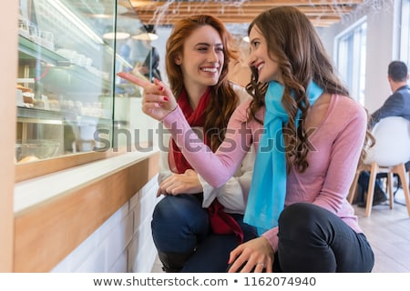 Two cheerful young women in front of the showcase of a modern cafe Stock photo © Kzenon