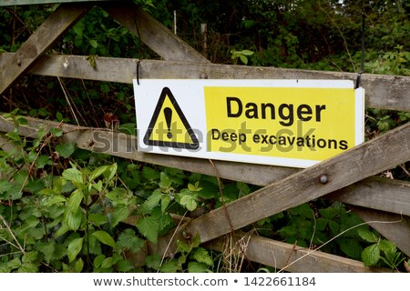 Warning sign - Danger Deep Excavations - on a wooden gate Stock photo © sarahdoow