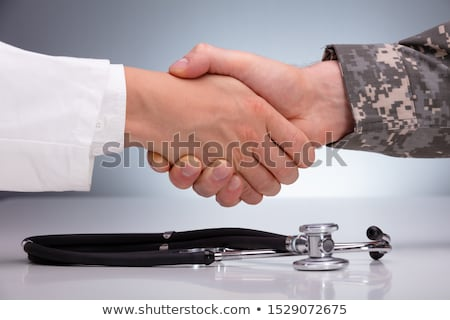Doctor And A Military Man Shaking Hands Over The Stethoscope Stock photo © AndreyPopov