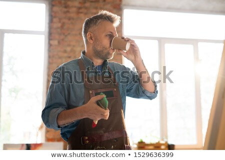 Mid-aged painter in workwear drinking hot coffee at break by workplace Stock photo © pressmaster