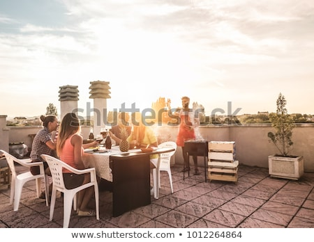 happy friends with drinks or bbq party on rooftop Stock photo © dolgachov
