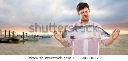 недовольный молодым человеком размер рыбы пляж Сток-фото © dolgachov