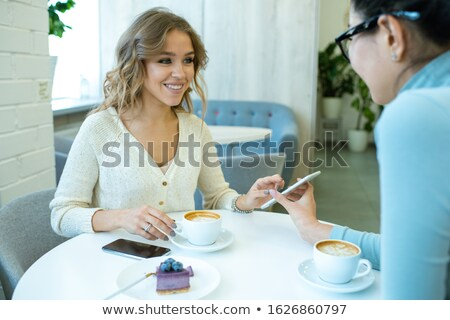 Cheerful girl looking at her friend while scrolling through photos in smartphone Stock photo © pressmaster