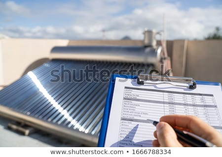 Plumber Looking At Solar Energy Electric Boiler Stock photo © AndreyPopov