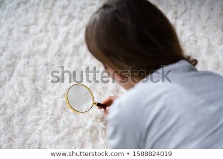 Vrouw naar tapijt vergrootglas jonge vrouwelijke Stockfoto © AndreyPopov