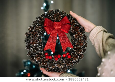 Woman's hands hold round wreath from dry twigs with bow. Stock photo © artjazz