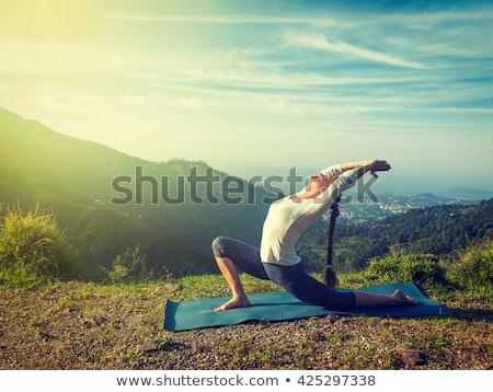 Sporty fit woman practices yoga asana Anjaneyasana in mountains Stock photo © dmitry_rukhlenko