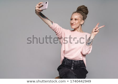 Girl with dreadlocks and piercing using mobile phone Stock photo © deandrobot