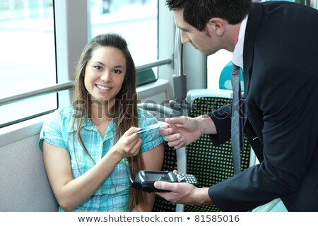 A young female passenger showing her card to a controller on a bus or a tramway. Stock photo © photography33