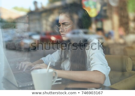 young woman behind window with a cup of coffee or tea stock photo © stokkete