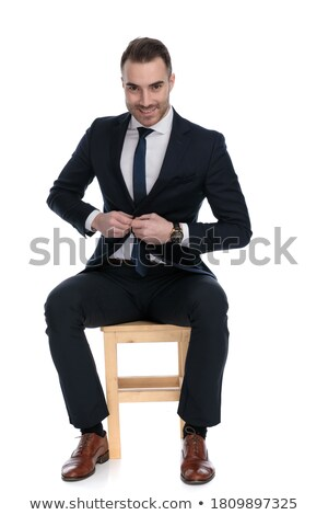 man sitting on a chair while unbuttoning his jacket Stock photo © feedough