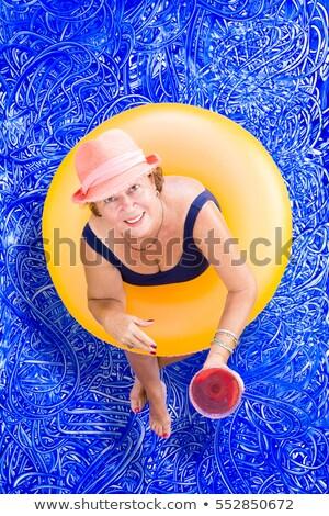 Elderly lady drinking pina colada in the pool Stock photo © ozgur