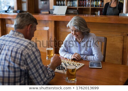 friends playing chess while having glass of beer in bar stock photo © wavebreak_media
