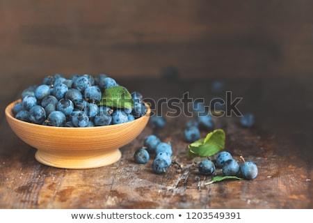 Autumn harvest blue sloe berries on a wooden table background. C Stock photo © artsvitlyna