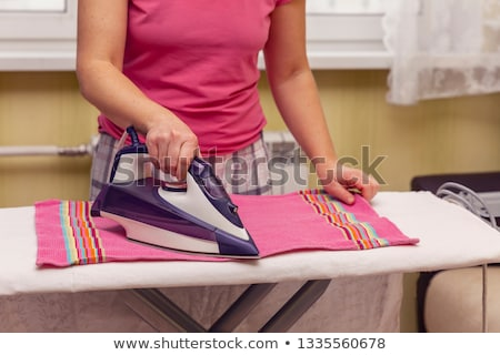 Kobieta gospodyni domowa ręcznik żelaza domu Zdjęcia stock © dolgachov