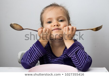 furious little girl waiting for dinner holding a fork in the hand stock photo © lopolo