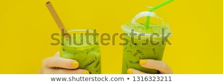 Green tea latte with ice in mason jar and in a plastic cup in hands on yellow background. Homemade I Zdjęcia stock © galitskaya