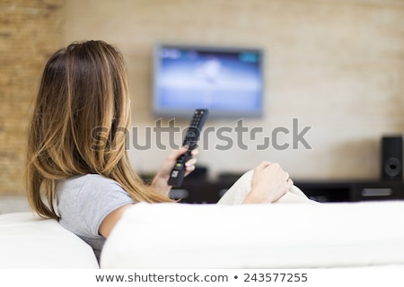 Women watching TV on the sofa at home with remote control Сток-фото © Lopolo