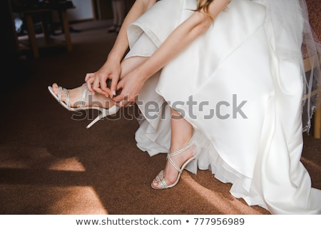 beautiful bride in a dress puts on red shoes Stock photo © ruslanshramko