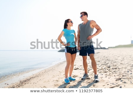 Сток-фото: Happy Couple In Sports Clothes And Shades On Beach