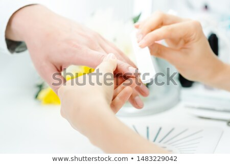 Woman filing fingernails of a man in nail parlor Stock photo © Kzenon