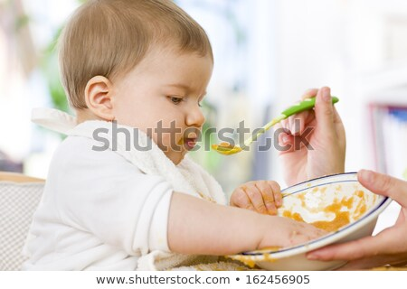 cute messy baby boy playing with food while eating stock photo © lichtmeister