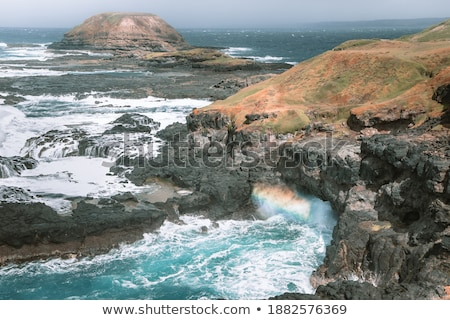 waves crashing on coast cliffs with rainbow Stock photo © morrbyte