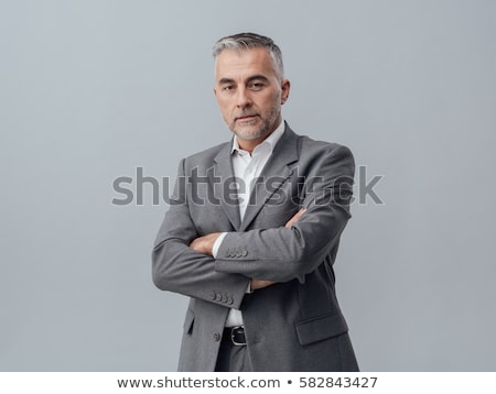 Matured businessperson posing with crossed arms stock photo © stockyimages