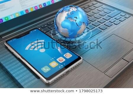 Mobile phone of electronics. Earth model tablet computer and mob Stock photo © kolobsek