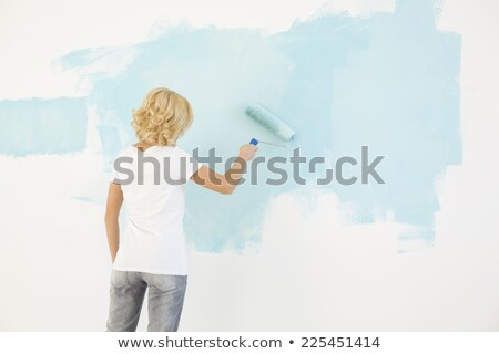 woman holding paint roller rear view stock photo © cherezoff