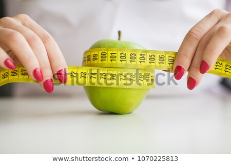 Stock foto: Woman Eating Green Apple And Holding Scales