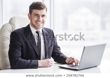 happy young business man sitting and thinking stock photo © feedough
