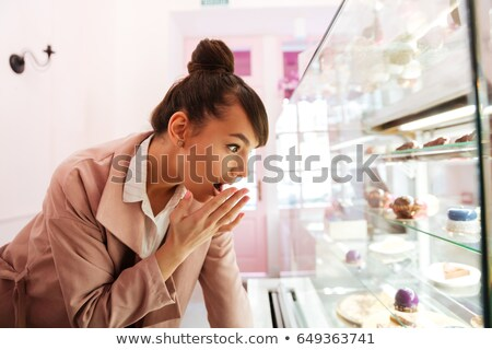 Woman standing in front of the glass showcase with pastries indoors Stock photo © deandrobot